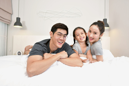 Portrait of beautiful young asian parents and daughter looking at camera and smiling while lying together in bed Stockfoto