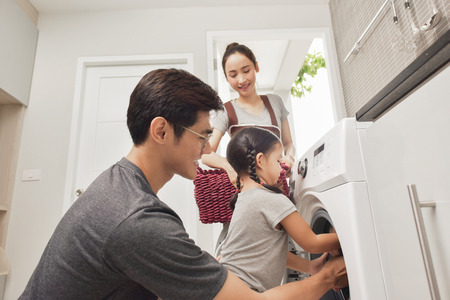 Happy Family loading clothes into washing machine in home