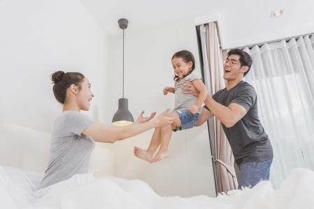 幸せな愛情のある家族。若い母親と父親は寝室で娘と遊んでいます。両親はベッドの上に楽しんでいます。