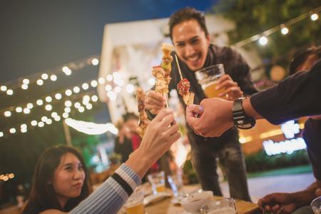 Grupo feliz de los amigos que tuesta y que bebe la cerveza en el partido del Bbq, estilo de la vendimia. Foto de archivo - 80248866