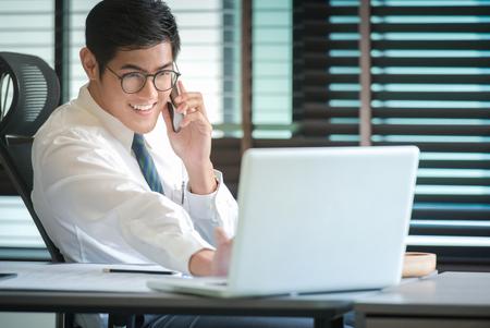 ビジネスマンは、スマート フォン、ノート パソコン投資チャートを分析します。会計