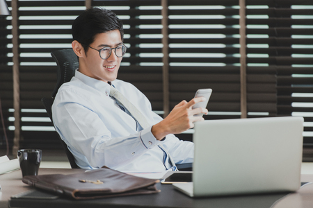 Asian businessman using his smartphone,computer in his office