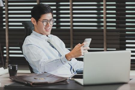彼のスマート フォンは、彼のオフィスにあるコンピューターを使用して、アジア系のビジネスマン