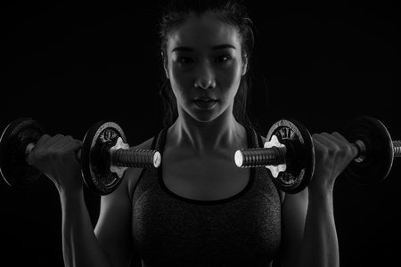 Beautiful girl exercising squatting with dumbbells,sport, fitness, bodybuilding,black and white,healthy and lifestyle concept.