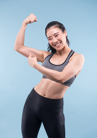 Cheerfully smiling asian sporty woman demonstrating biceps on blue background.