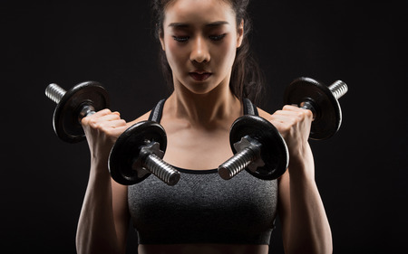 Beautiful girl exercising squatting with dumbbells on black. Stock Photo