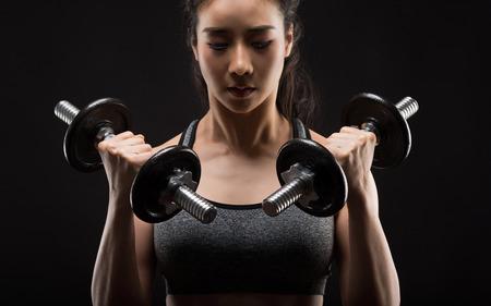 Beautiful girl exercising squatting with dumbbells on black. Stockfoto