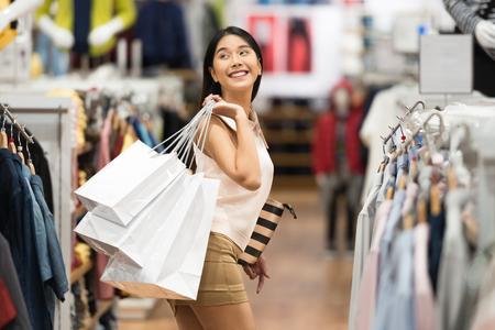 高級衣料品店で買い物袋を持つ若い幸せな女性。 写真素材