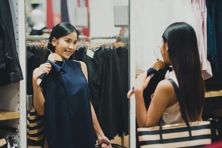 Woman shopping choosing dresses looking in mirror uncertain. Beautiful young asian shopper in clothing store. Banco de Imagens
