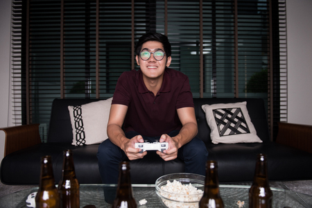 The avid gamer,young asian man playing video games at home Stock Photo