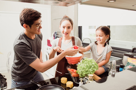 Cute little girl and her beautiful parents are smiling while cooking in kitchen at home Standard-Bild