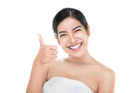 Beautiful asian woman perfect skin showing thumbs up isolated with clipping path.