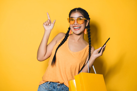 Beautiful young woman with shopping bags using her smart phone on yellow background.Shopaholic shopping Fashion. 스톡 콘텐츠