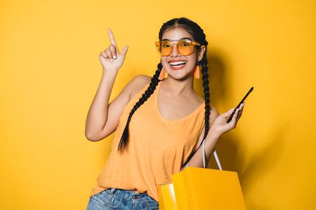 Schöne junge Frau mit Einkaufstaschen unter Verwendung ihres Smartphones auf gelbem Hintergrund. Shopaholic Einkaufsmode.