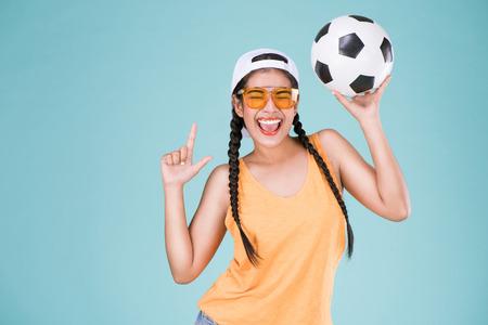 Fanático de la mujer linda del campeonato de fútbol. Colocar la bola de la explotación agrícola de la muchacha sobre fondo azul.