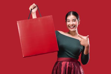 Retrato de mujer linda joven feliz posando con bolsas de la compra sobre fondo rojo. Foto de archivo