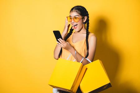 Belle jeune femme avec des sacs à provisions à l'aide de son téléphone intelligent sur fond jaune.Shopaholic shopping Fashion.