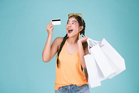 portret van vrolijke jonge brunette vrouw met creditcard en boodschappentassen op blauwe achtergrond.