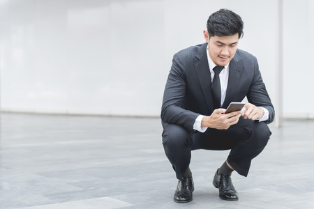 Young businessman sitting and reading a message on his smartphone
