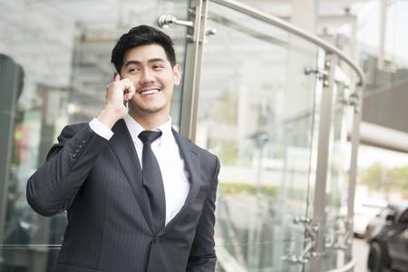 Businessman smiling and talking on phone at sidewalk of the modern building Banco de Imagens