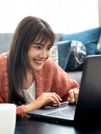Young Asian woman works from home on tablet computer, enjoys morning weekend, work from home concept.