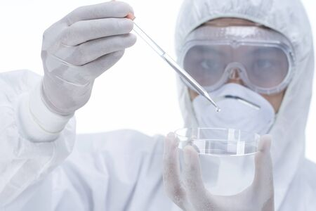 Chemist in laboratory checking test tubes,Portrait of Asian biotechnologist examining test-tube with a liquid on white background.