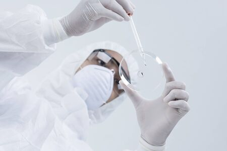 young man scientist or laboratory worker holding a Petri dish , healthcare, science and medicine. Banco de Imagens
