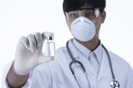 Chemist in laboratory checking test tubes,Shallow DOF the Focus is on the little bottle and the hand. Banco de Imagens