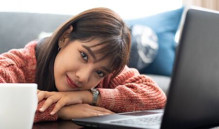 Young Asian woman works from home on computer Labtop, enjoys morning weekend, work from home concept.