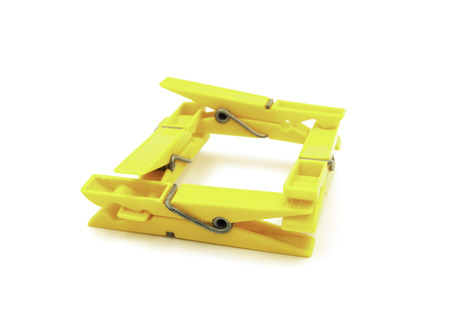 Four yellow pegs on white background - square