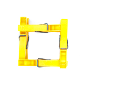 Four yellow pegs on white background - square from top Stock Photo
