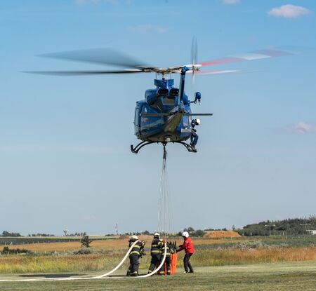 Police helicopter and firefighters filling water bucket