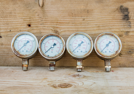 gauges: Old pressure gauges on wood background Stock Photo