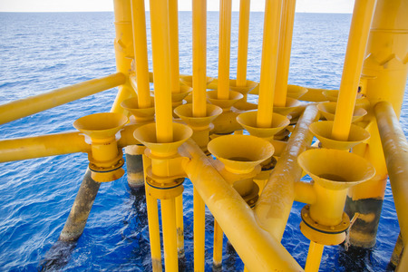 wellhead: Aligned Oil and Gas Production slots on the sea background in Offshore wellhead remote platform, Energy and petroleum industry.