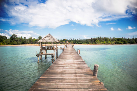Jetty to a tropical beach with blue sky background
