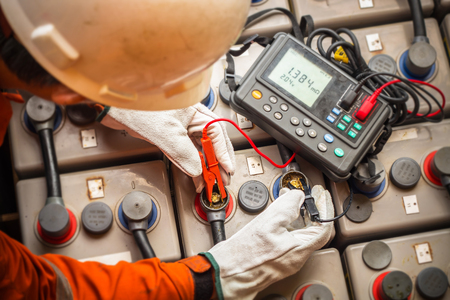 resistance: electrician using the digital battery tester  to check the resistance and voltage of batteries