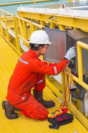 test probe: Electrician,Electrician using the digital multimeter to check the resistance and voltage of electric systems in oil and gas industrail.