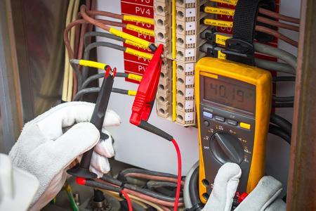Elektricien, elektricien met behulp van de digitale multimeter om de weerstand en de spanning van de elektrische systemen in olie en gas industrail controleren. Stockfoto