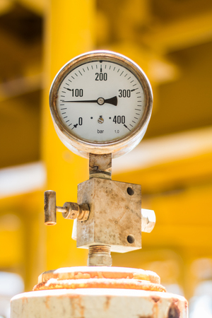 abstract soft focus pressure gauge with pipeline construction at offshore platform industrial background concept.