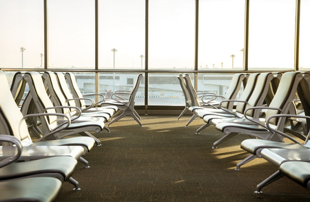 contemporary lounge with seats in the airport during sun set or sun rise time, worm tone