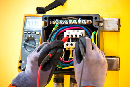electrician,close up hand of electrician checking voltage by multimeter