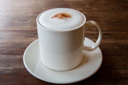 Cappuccino coffee in white cup on wooden table