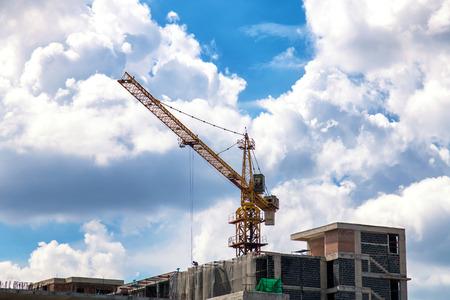 Crane and building under construction against blue sky Stok Fotoğraf