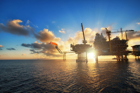 Silhouette,Offshore oil  platform in sunset or sunrise time. Construction of production process in the sea. Power energy of the world. Stok Fotoğraf