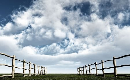 Two wooden fences lead towards the horizon and cloud filled sky