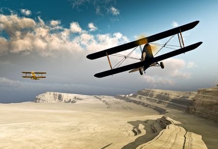 propellers: Two vintage WWI double wing planes flying over a canyon