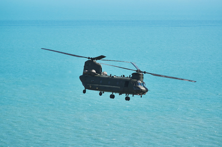 raf: EASTBOURNE, ENGLAND - AUGUST 14, 2015: RAF helicopter Chinook HC4 performs at the Airbourne airshow.RAF Chinooks provide heavy-lift support and transport across all branches of the British armed forces. Editorial