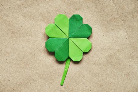 Green origami paper shamrock clover leaf on eco paper background.