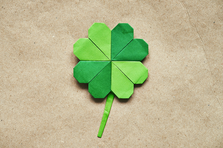 green day: Green origami paper shamrock clover leaf on eco paper background.