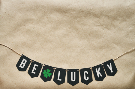 Be lucky banner string lettering. St. Patrick's Day eco craft paper background. Empty space for copy, text.